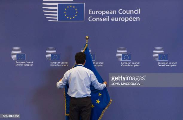 An official adjusts an EU flag in the lobby of the European Council building in Brussel on July 12 ahead of a summit of Eurozone heads of state The...