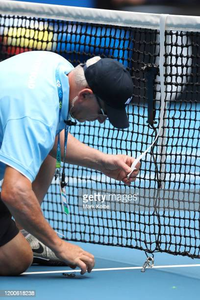 An official amends the net during the Women's Singles first round match between Marie Bouzkova of Czech Republic and Naomi Osaka of Japan on day one...