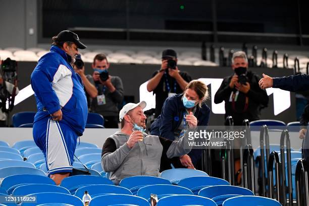 An official asks spectators to leave the arena due to Covid-19 lockdown restrictions in middle of the men's singles match between Serbia's Novak...