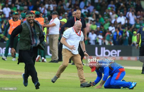 An official assists an Afghan player as a pitch invader runs on the field after the 2019 Cricket World Cup group stage match between Pakistan and...
