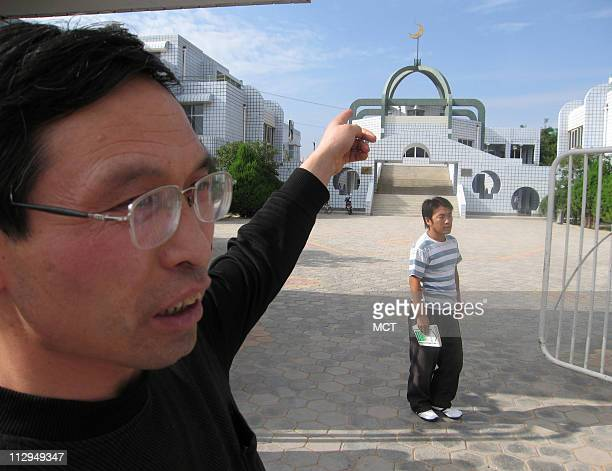 An official at the Tongxin Arab Language College Chen Jianyi points to the mosque that is at the center of the institution The college is in Tonxin a...