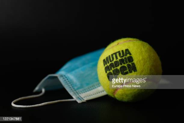 An official ball from the Mutua Madrid Open professional tennis tournament together with a surgical mask The competition will be 'played' virtually...