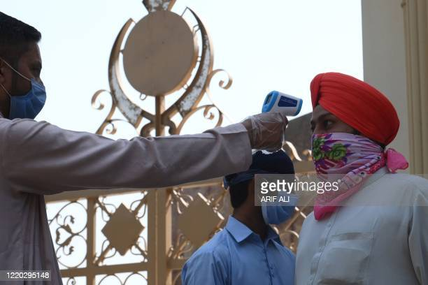 An official checks body temperature of a Sikh pilgrim arriving to attend a religious ceremony on the occasion of the 414th death anniversary of the...