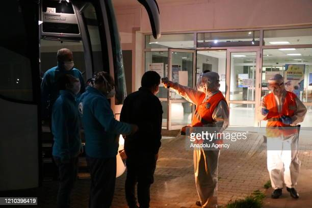 An official checks temperature of a Turkish citizen who was one of the passengers of Greek cruise ship, El. Venizelos, after the citizens brought by...