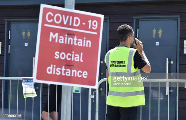 An official controls the use of public toilets by calling people from the queue and guiding them to a numbered cubicle as crowds of people gather on...