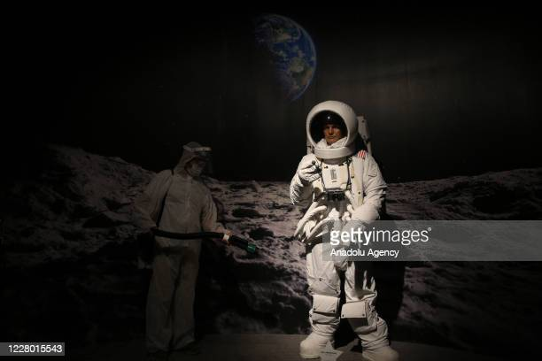 An official disinfects astronaut Neil Armstrong's wax sculpture within precautions against coronavirus pandemic at Wax Sculpture Museum of Antalya...