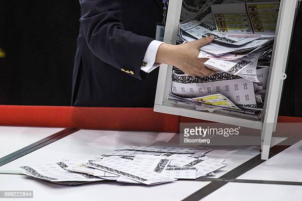 An official empties ballot papers for the Legislative Council election from a ballot box at the central counting station in Hong Kong China on Monday...