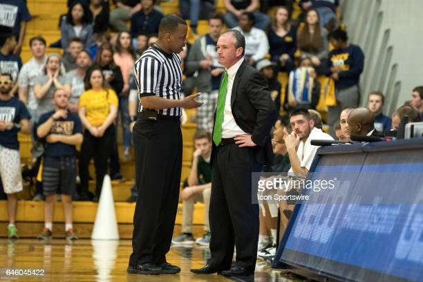 An official explains a foul call to Ohio Bobcats head coach Saul Phillips during the second half of the men's college basketball game between the...