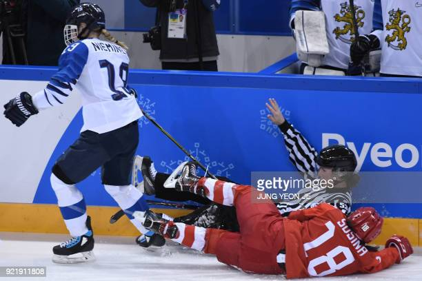 An official falls next to Russia's Olga Sosina as Finland's Petra Nieminen skates past in the women's bronze medal ice hockey match between Finland...