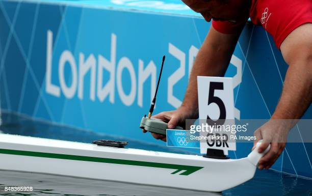 An official fits a GPS tracker to the boat of Great Britain's Alan Campbell prior to the heats of the men's single sculls during the first day of the...