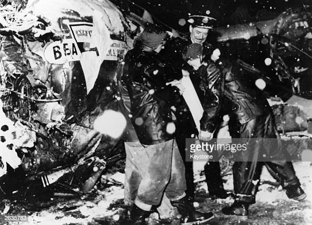 An official from British European Airways' Munich office with US firemen beside the wreckage of the BEA Elizabethan airliner which crashed in the...
