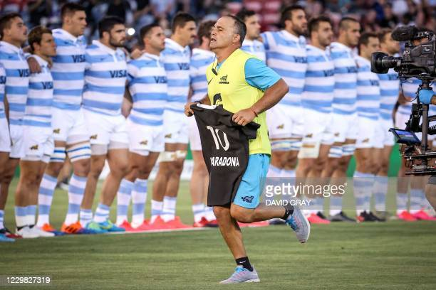 An official from the Argentina team carries an All Blacks jersey with the name Maradona and the number ten printed on it, as a tribute to the late...