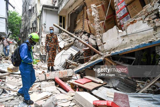 An official from the Criminal Investigation Department inspects the spot of a suspected gas explosion in Dhaka. At least seven people were killed and...