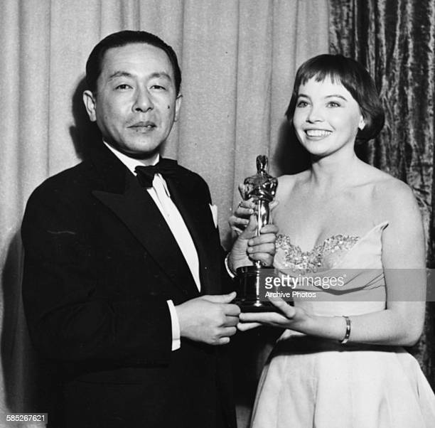 An official from the Japanese consul accepts the Best Foreign Language Oscar for the film 'Rashomon' from actress Leslie Caron, at the 24th Academy...