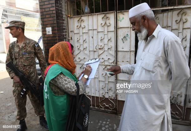 An official from the Pakistan Bureau of Statistics collects information from a resident during a census as army slodier stands guard in Karachi on...