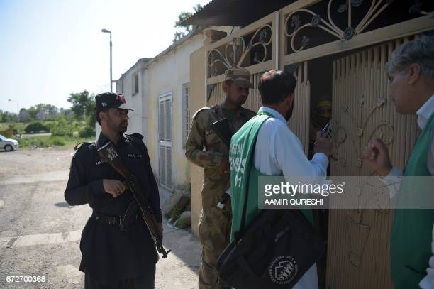 An official from the Pakistan Bureau of Statistics collects information from a resident as Pakistani soldiers stand guard during the second phase of...