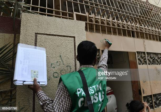 An official from the Pakistan Bureau of Statistics marks a house after collecting information from a resident during a census in Karachi on March 15...