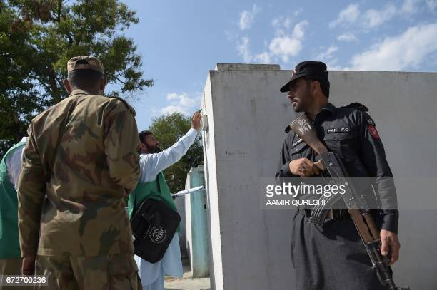 An official from the Pakistan Bureau of Statistics marks a house after collecting information from a resident as Pakistani soldiers stand guard...