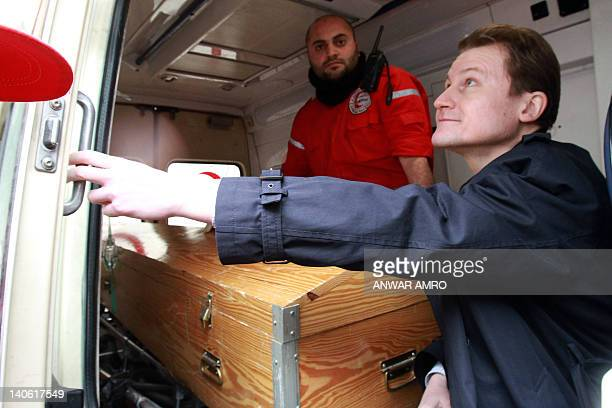 An official from the Polish embassy is seen with the coffin containing the remains of killed veteran US reporter Marie Colvin of the Sunday Times in...