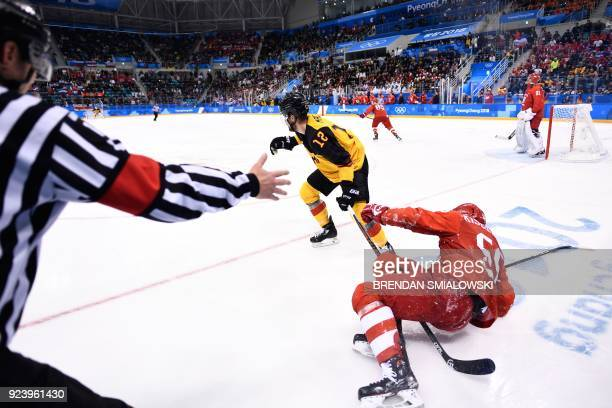 An official gestures after Germany's Brooks Macek and Russia's Bogdan Kiselevich collided in the men's gold medal ice hockey match between the...