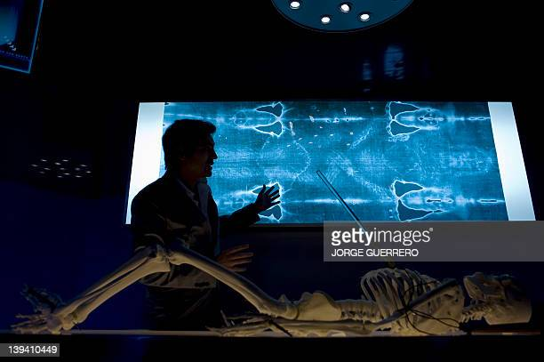 An official gestures as he speaks next to a facsimile of 'The Shroud of Turin' at the Cathedral of Malaga on February 20 2012 AFP PHOTO/ JORGE...
