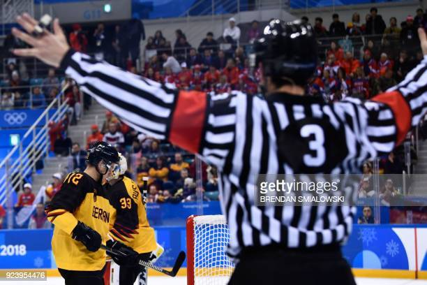An official gestures in front of Germany's Brooks Macek and Danny aus den Birken in the men's gold medal ice hockey match between the Olympic...