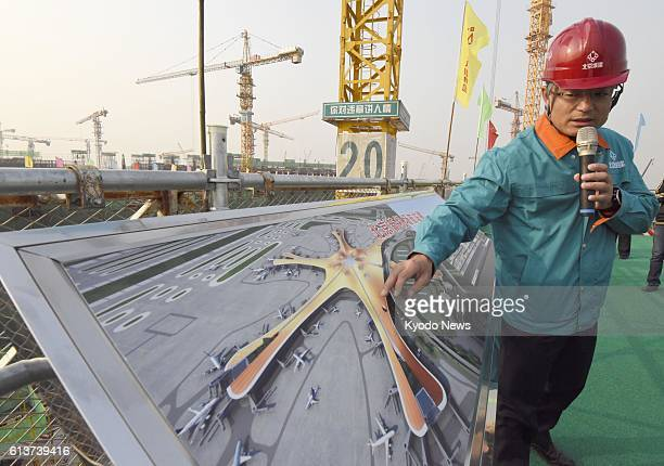 An official gives a briefing on a new airport in Beijing on Oct 10 when the construction site in the south of the capital opened to some foreign...