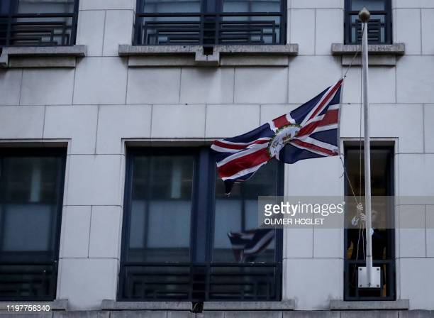 An official handles a United Kingdom flag after removing the European Union flag at the United Kingdom Representation to the EU building in Brussels...