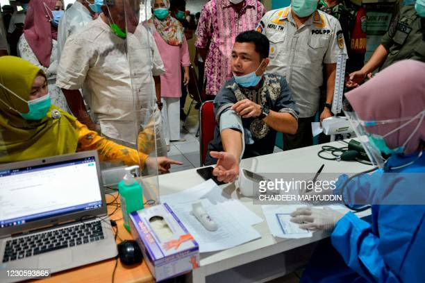 An official has a blood pressure test before receiving the Sinovac vaccine against the Covid-19 coronavirus at Meuraxa Hospital in Banda Aceh on...