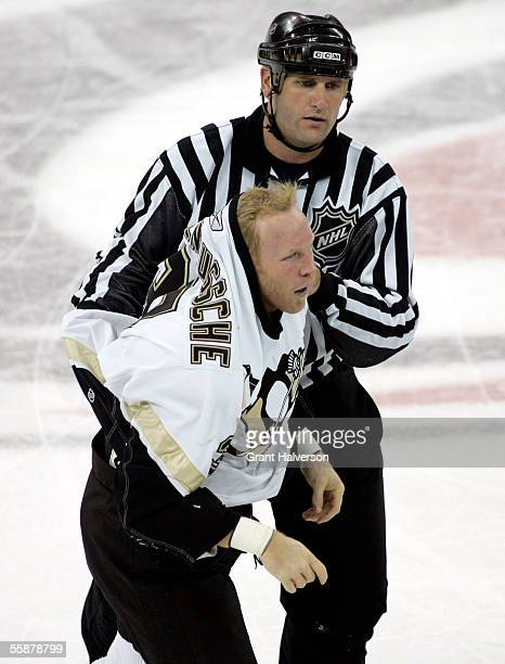 An official helps Ryan VandenBussche of the Pittsburgh Penguins off of the ice after a fight during an overtime loss to the Carolina Hurricanes on...