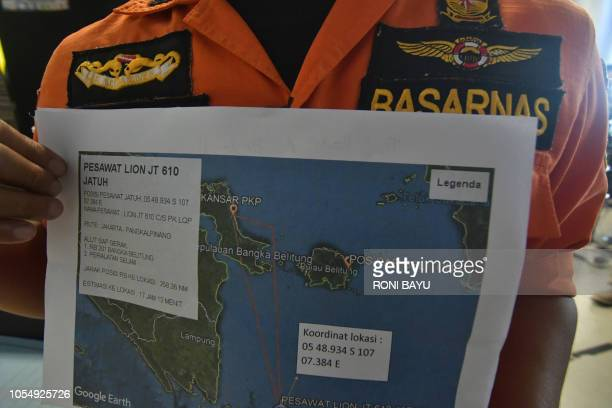 An official holds a map of ongoing search efforts to locate the wreckage of Lion Air flight JT 610 at Pangkal Pinang airport in Bangka Belitung...