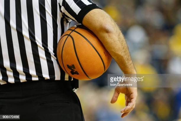 An official holds the ball while waiting for play to resume during a regular season Big 10 Conference basketball game between the Illinois Fighting...