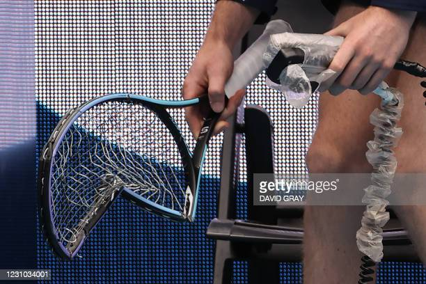 An official holds the racquet of Germany's Alexander Zverev after he smashed it after a point against Marcos Giron of the US during their men's...