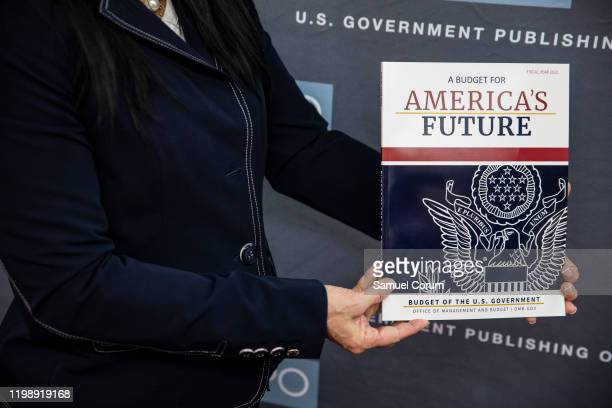 An official holds up a copy of US President Donald Trump's proposed budget for the US Government for the 2021 Fiscal Year at the Government...