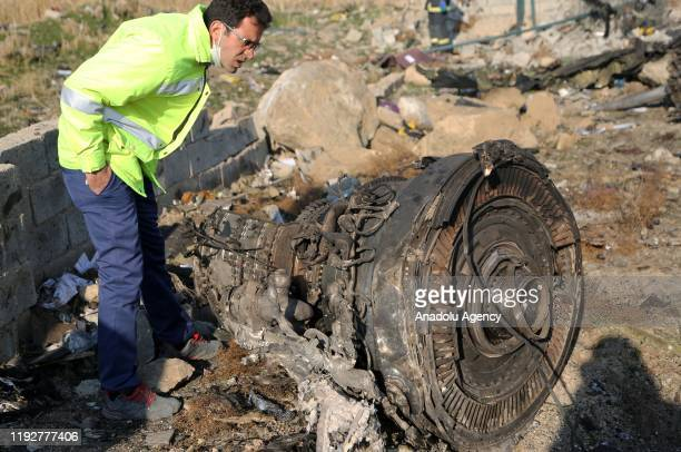 An official inspects a piece of the plane at site after a Boeing 737 plane belonging to Ukrainian International Airlines crashed near Imam Khomeini...
