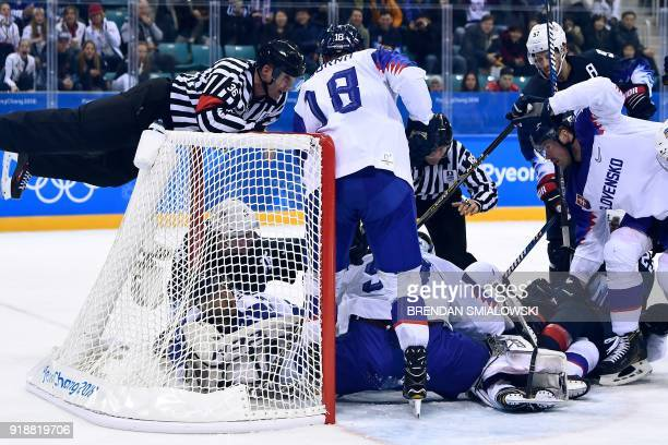 An official judges a pile up in the men's preliminary round ice hockey match between the US and Slovakia during the Pyeongchang 2018 Winter Olympic...