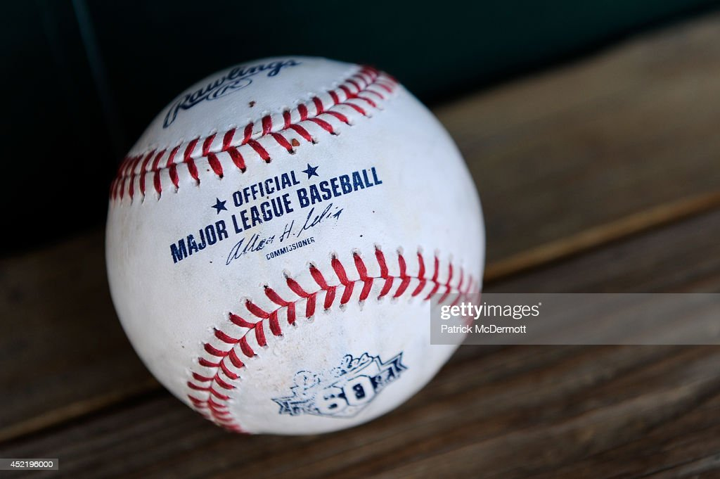 An official Major League Baseball sits in the dugout during batting practice before the start of a game between the Washington Nationals and Baltimore Orioles at Oriole Park at Camden Yards on July 10, 2014 in Baltimore, Maryland.