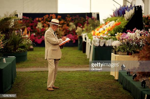 An official makes notes as he views the flowers displayed in the RHS Floral Marquee during the press preview day of the Hampton Court Palace Flower...