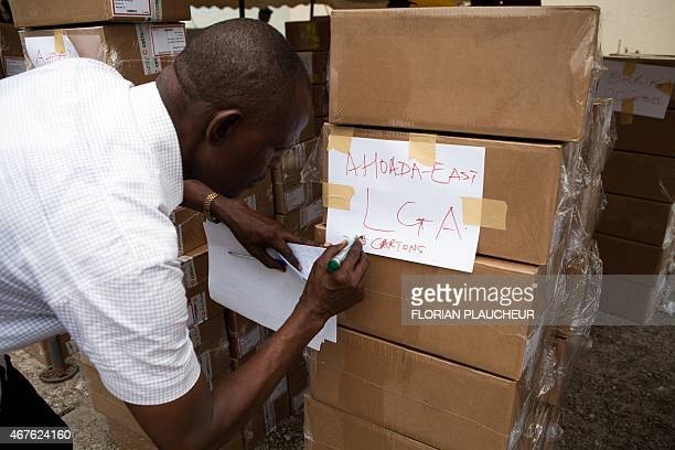 An official marks boxes as voting materials are prepared at the Independent National Electoral Commission offices in the oil hub of Port Harcourt on...