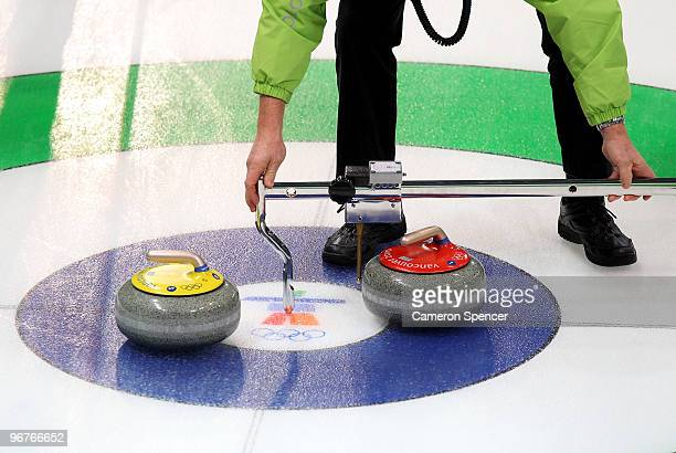 An official measures distances between stones and the centre during the women's curling round robin game between Japan and the United States on day 5...