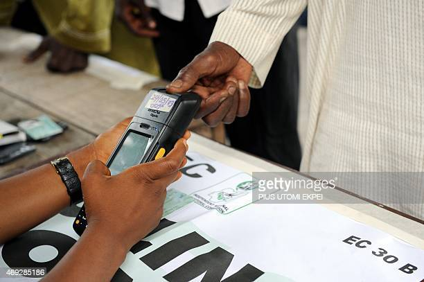An official of Independent National Electoral Commission registers thumb print of a voter with biometric system at a polling station at Apapa...