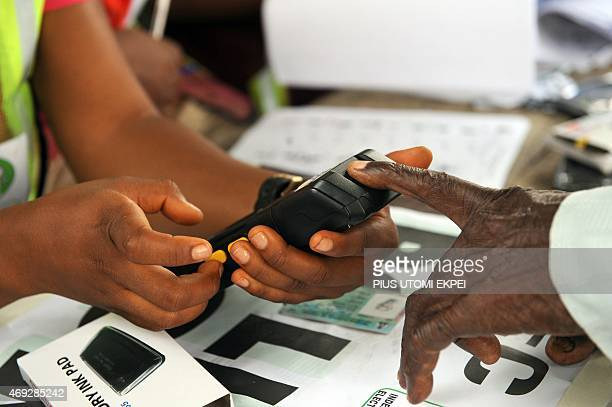 An official of Independent National Electoral Commission registers the finger print of a voter with biometric system at a polling station at Apapa...