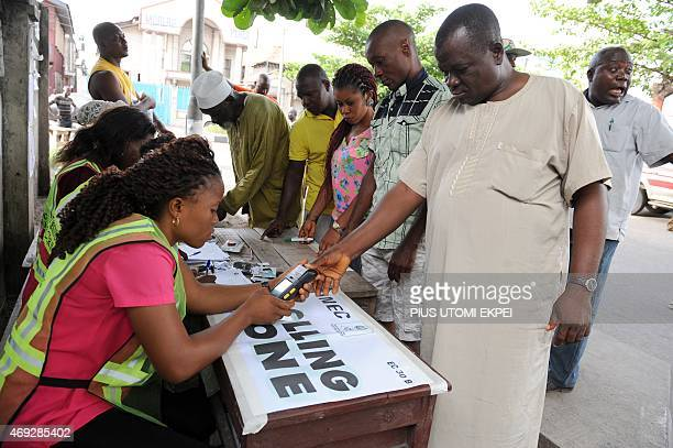 An official of Independent National Electoral Commission registers the thumb print of a voter with biometric system at a polling station at Apapa...