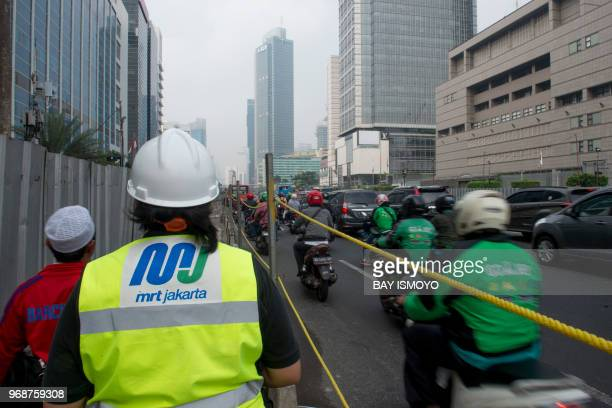 An official of Jakarta's MRT project walks along the construction site in Jakarta on June 7 2018 as the right side showing heavy traffic Deep below...