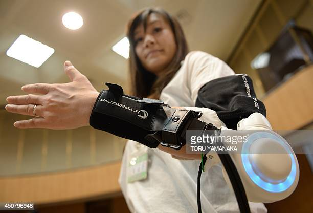 An official of Kawasaki City demonstrates a new powered exoskeleton to assist movement of an arm developed by Japan's robot suit venture Cyberdyne...