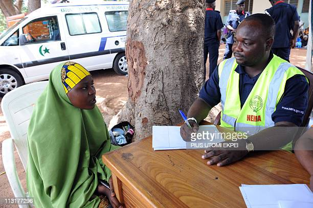 An official of National Emergency Management Agency interviews at Hajj Camp in Kaduna a female displaced by violence that erupted after President...