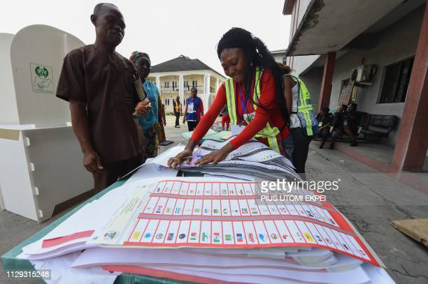 An official of Nigeria's Independent National Electoral Commission attends to a voter in Port Harcourt Rivers State on March 9 as voting has started...
