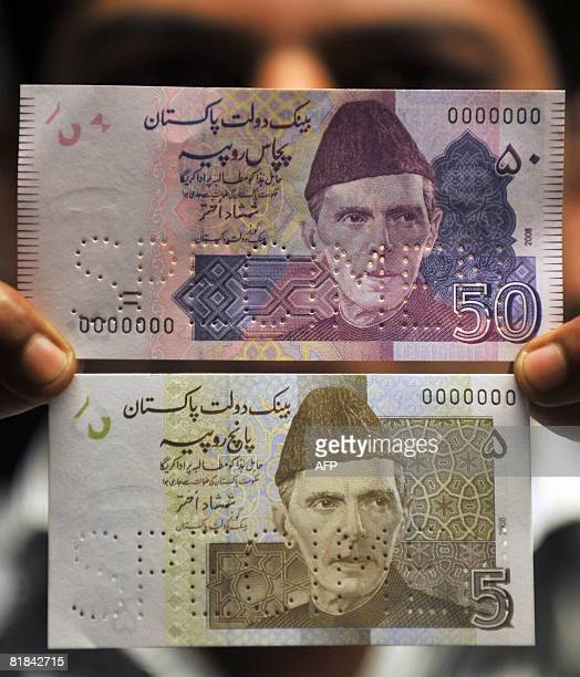 An official of Pakistan's central bank the State Bank of Pakistan shows new currency notes of five and fifty rupee denominations at a press...