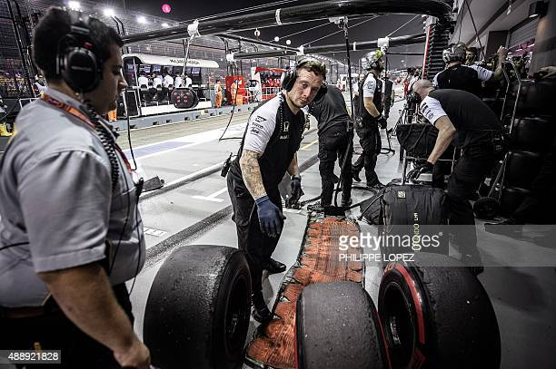 An official of Pirelli tyres looks on as McLaren Honda's team members handle tyres during the free practice session of the Formula One Singapore...