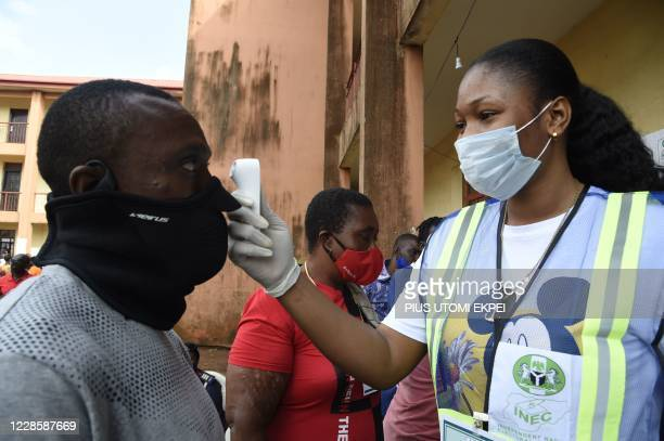An official of the Independent National Electoral Commission test a voter with infrared thermometer during the Edo State governorship elections in...